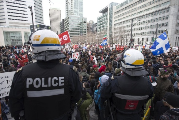 Police watch protesters gather as thousands join a student-led protest against the provincial government's austerity measures in Montreal