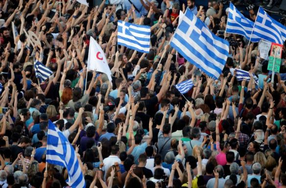 Protestors wave Greek flags in front of the parliament building during an anti-austerity rally in Athens, Greece, July 3, 2015. Tsipras, elected in January on a promise to end six years of austerity, extolled a packed Syntagma square in central Athens to spurn the tough terms of an aid deal offered by international creditors to keep the country afloat.  Photo:Reuters
