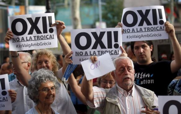"""People hold signs supporting Greece during a pro-Greece protest in front of European Union office in Barcelona, Spain, July 3, 2015. The sign reads """"No. No to troika"""".  Photo:Reuters"""