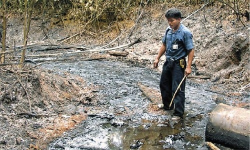Achuar leader Carlos Sandi observes the damage left behind by extractionist oil companies.| Photo: Reuters