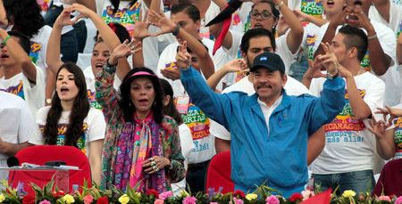 President Daniel Ortega and first lady  Rosario Murillo greet supporters during celebrations to mark the 37th anniversary of the Sandinista Revolution at the Juan Pablo II square in Managua